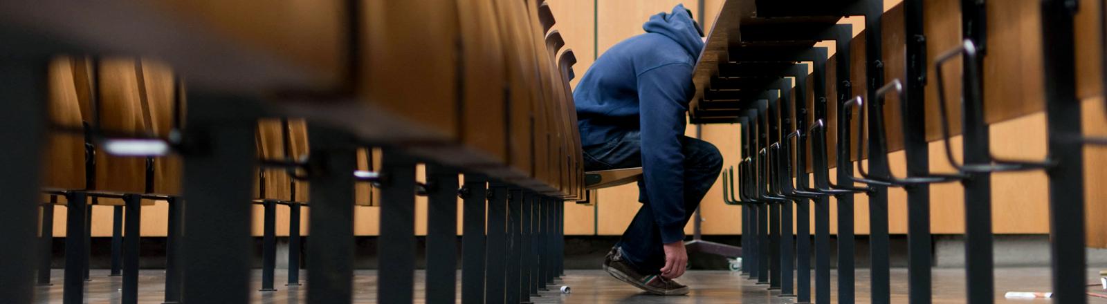 Ein Student sitzt erschöpft in einem Hörsaal.