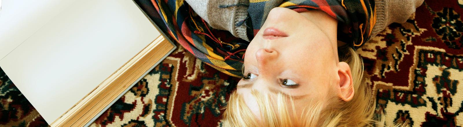 Eine junge Frau liegt auf dem Teppich, neben ihr ein leeres Buch.