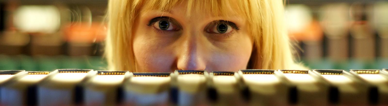 Eine Frau schaut in einer Bibliothek durch die Bücherreihen.