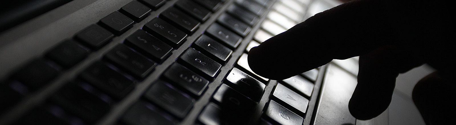 Hand tippt auf Tastatur