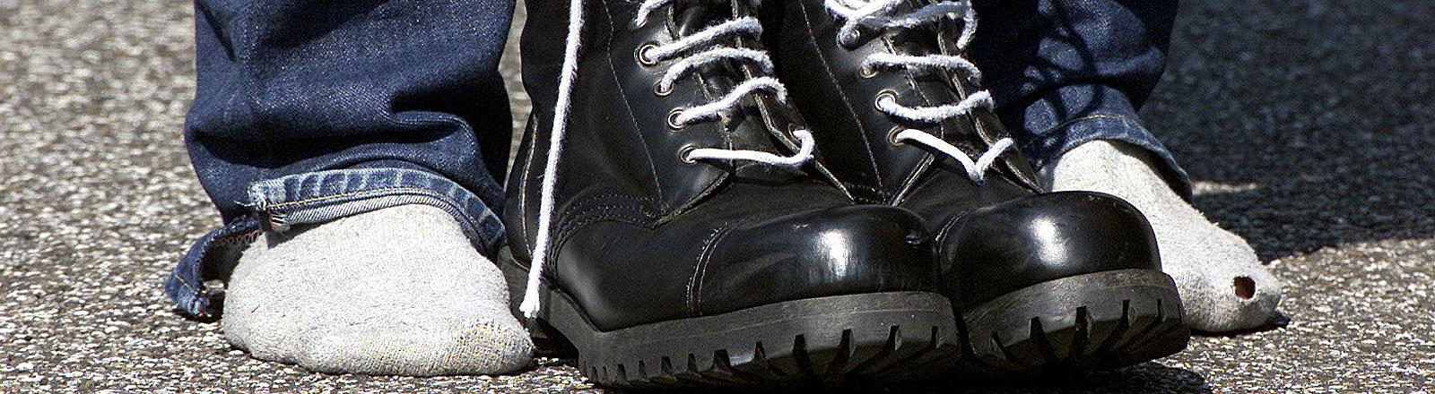 Springerstiefel stehen neben besockten Füßen