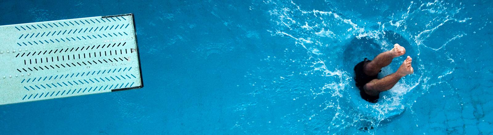 EIn Mann ist vom Sprungbrett gesprungen, man sieht noch die Beine, bevor sie ins Wasser eintauchen.