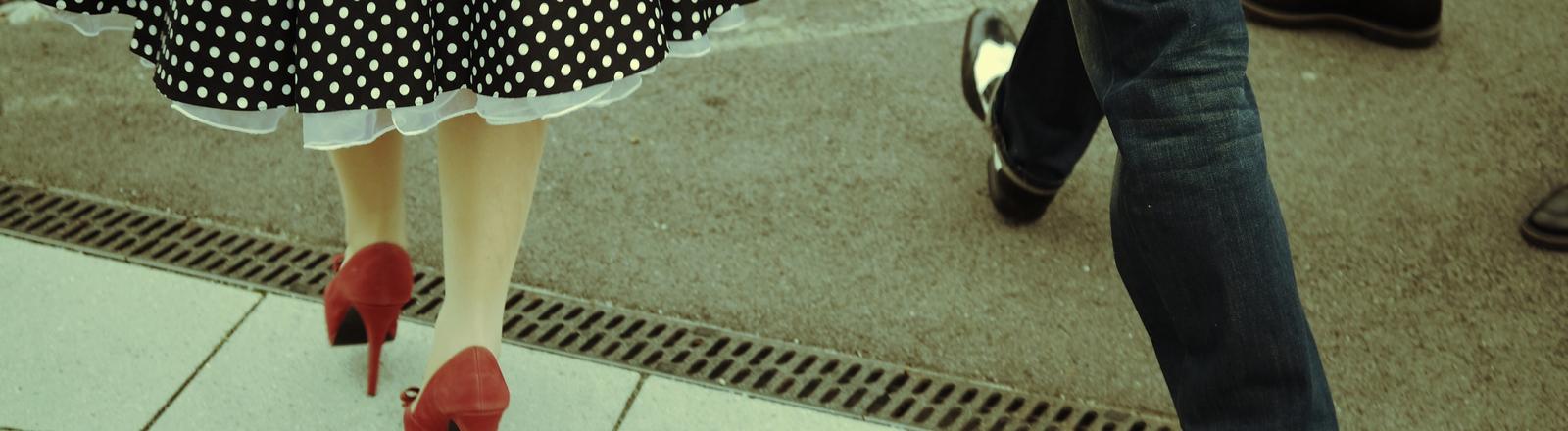 Füße in Pumps und schicken Schnürschuhen.