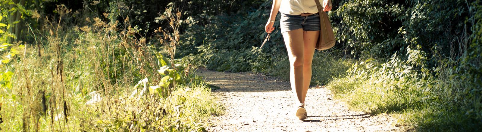 Frau, die durch einen sommerlichen Wald läuft.