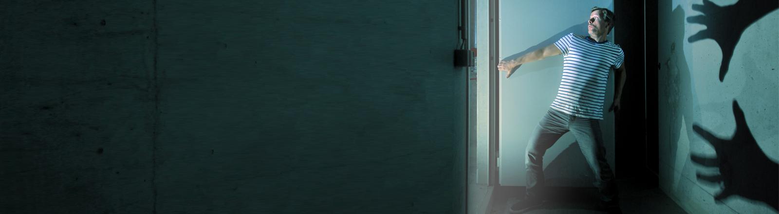 Ein Mann schaut mit Entsetzen in einen Raum, von hinten nähern sich gruselige Schattenhände.