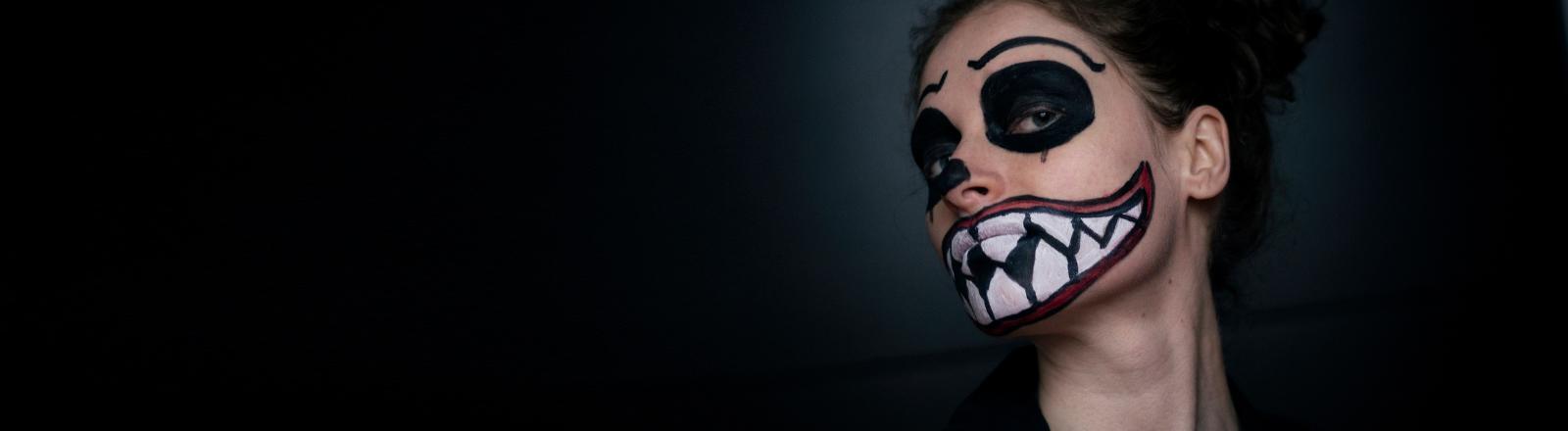 Eine Frau mit aufgemalter Horror-Fratze.