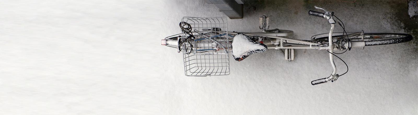Ein Fahrrad steht einsam im Schnee herum.