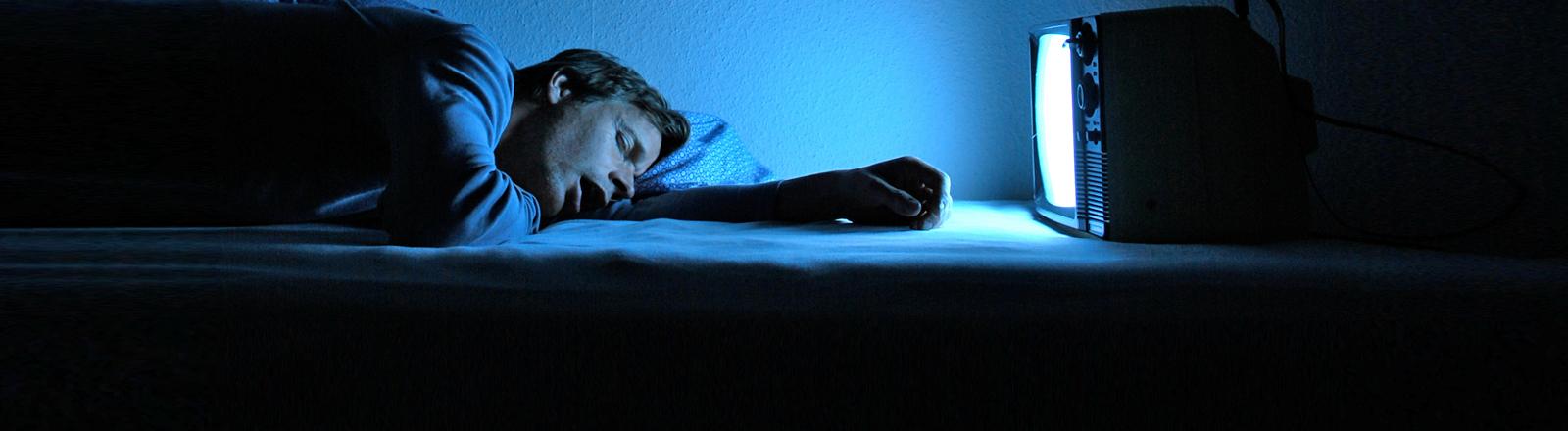 Ein Mann ist vor seinem flimmernden Fernseher eingeschlafen.