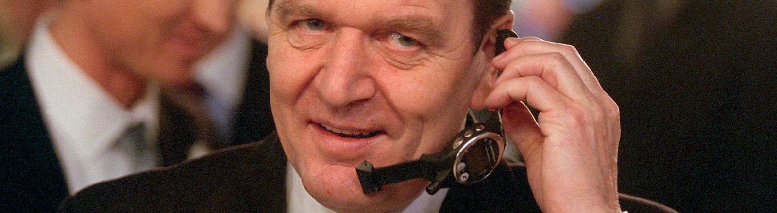 Schmunzelnd telefoniert Bundeskanzler Gerhard Schröder am 24.2.2000 in Hannover bei seinem Eröffnungsrundgang auf der Computermesse CeBIT mit einem Watchphone von Motorola - ein Handy in Form einer Armbanduhr.
