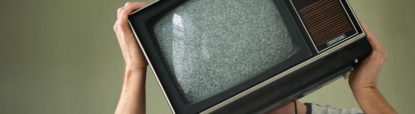 Ein Mann hält sich einen Fernseher vor das Gesicht.