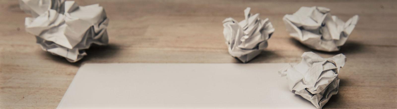 Auf einem Tisch liegt ein Blatt Papier, daneben ein paar zerknüllte Zettel.