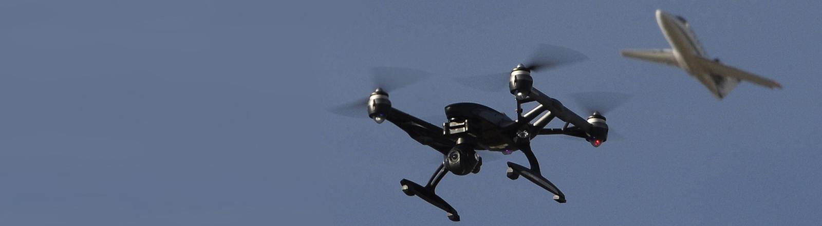 Ein Drohnen-Quadrokopter schwebt vor einem Flugzeug