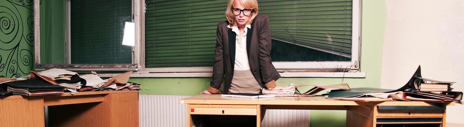 Eine Frau steht hinter einem sehr unordentlichen Schreibtisch.