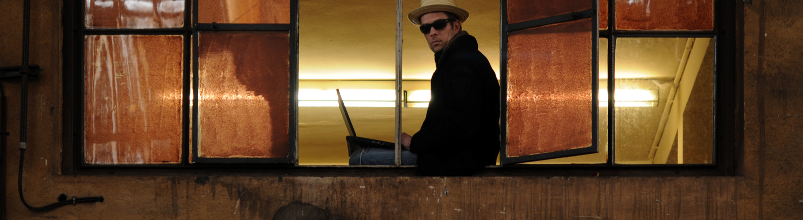 Ein Mann sitzt mit dem Laptop im offenen Fensterrahmen.
