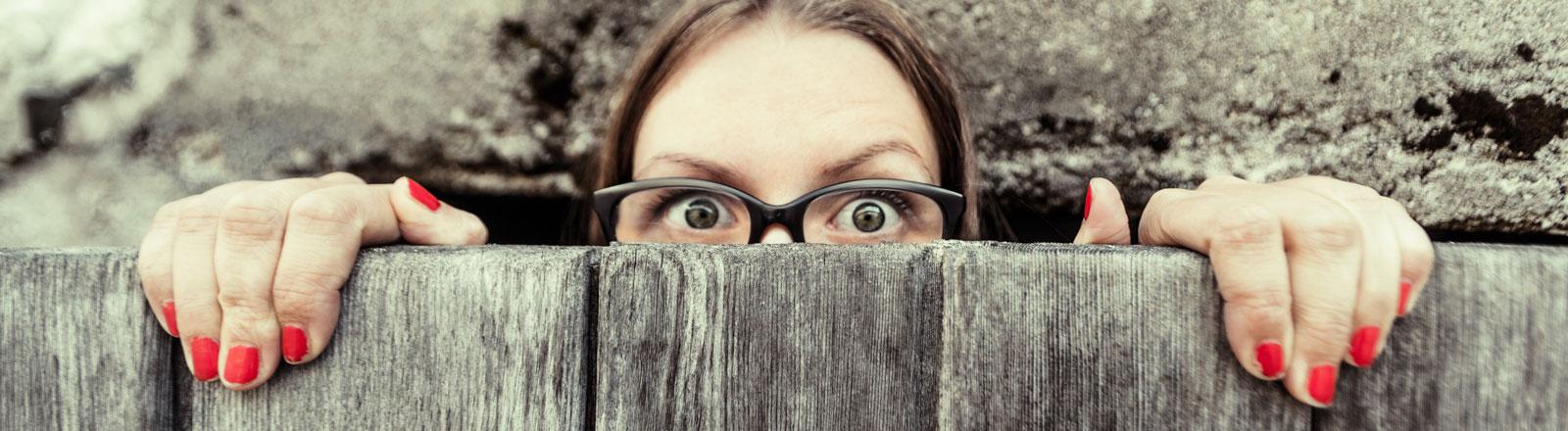 Eine Frau guckt ängstlich über einen Zaun.