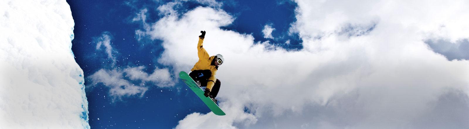 Ein Mann springt auf einem Snowboard.