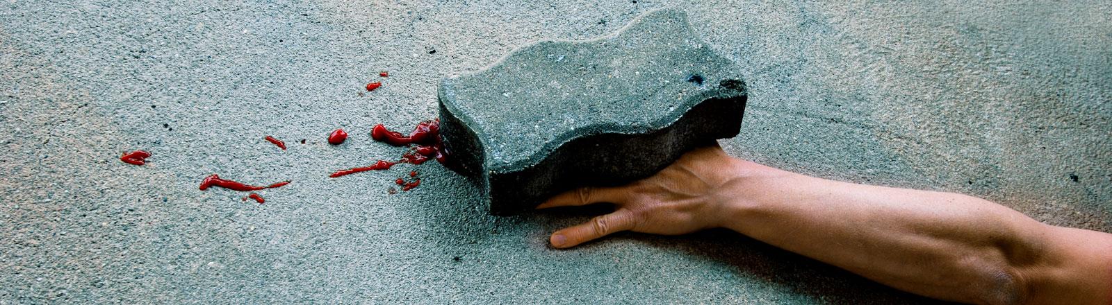 Ein Stein auf einer Hand. Die Hand ist blutig.