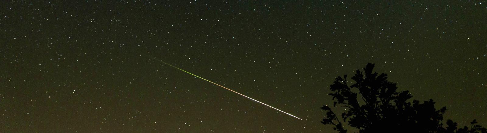 Eine Sternschnuppe am nächtlichen Sternenhimmel.