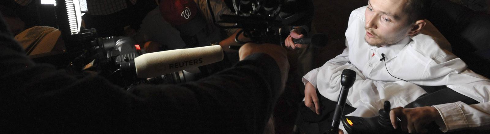 Waleri Spiridonow sitzt in einem Rollstuhl. Er ist umgeben von Journalisten, die ihm Mikrofone vor das Gesicht halten.