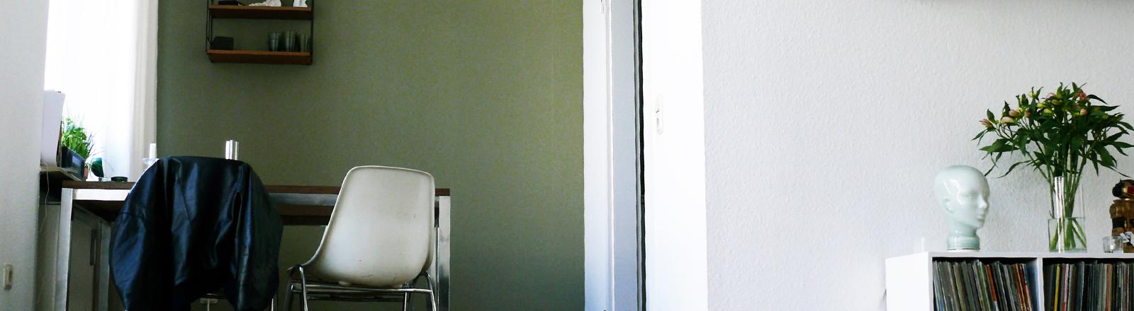 Wohn- und Esszimmer mit Tisch, Stühlen und Sideboard.