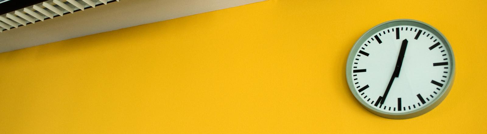 Eine Uhr an einer gelben Wand