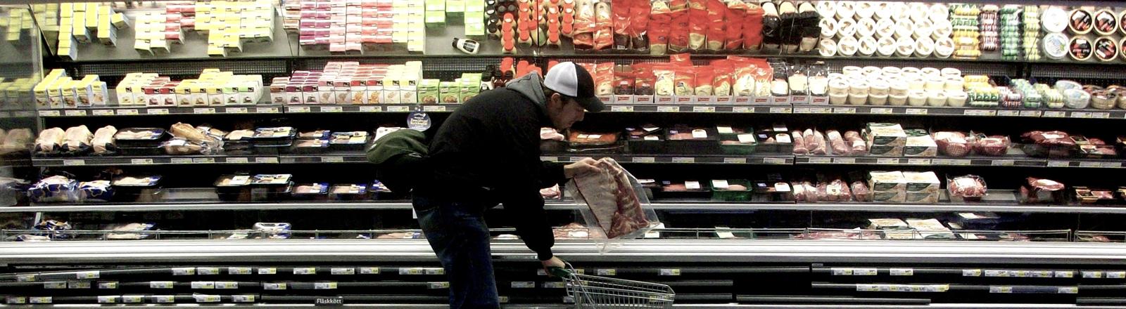 Mann vor der Kühltheke im Supermarkt