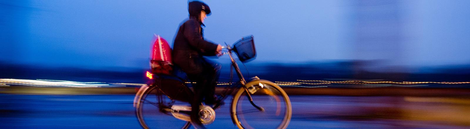 Frau fährt bei Regen in Hannover Fahrrad.