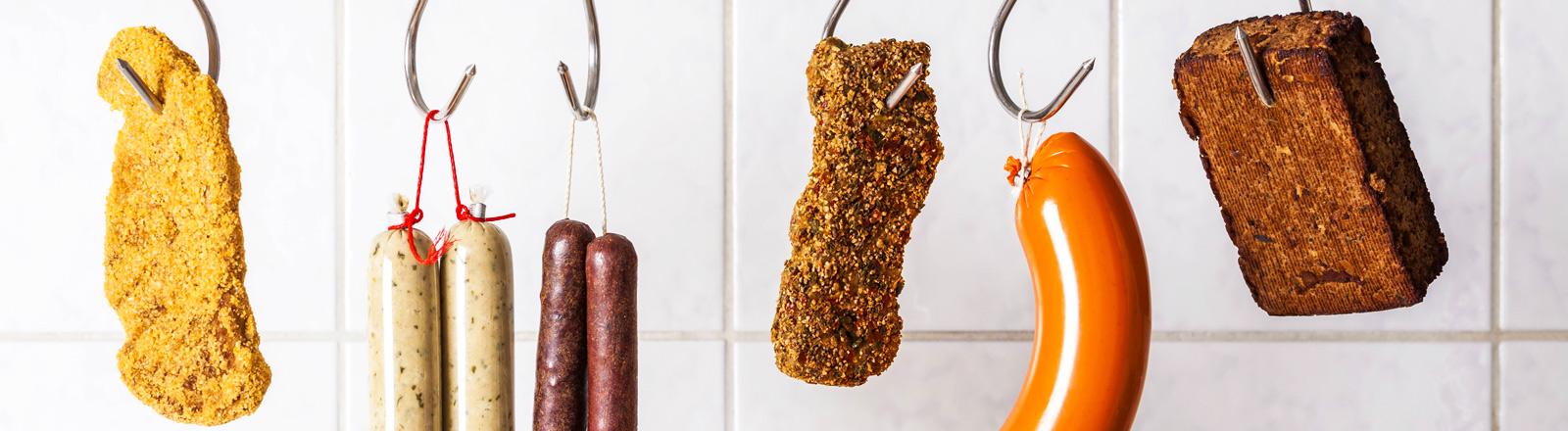 Unterschiedliche vegetarische Fleischersatzprodukte hängen an einem Haken