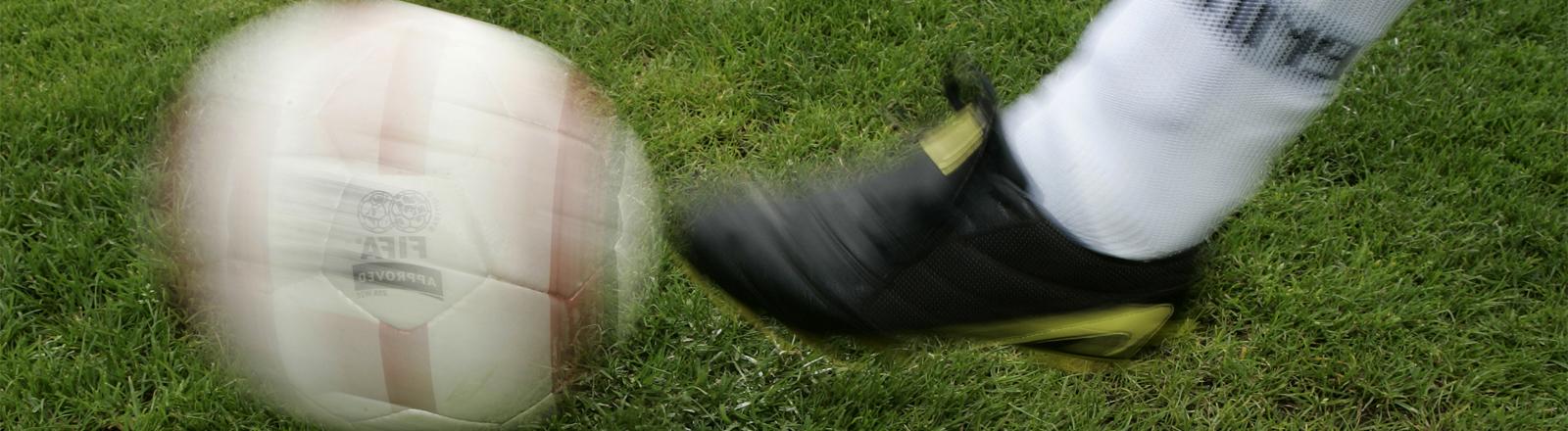 Fußballer kickt gegen Ball
