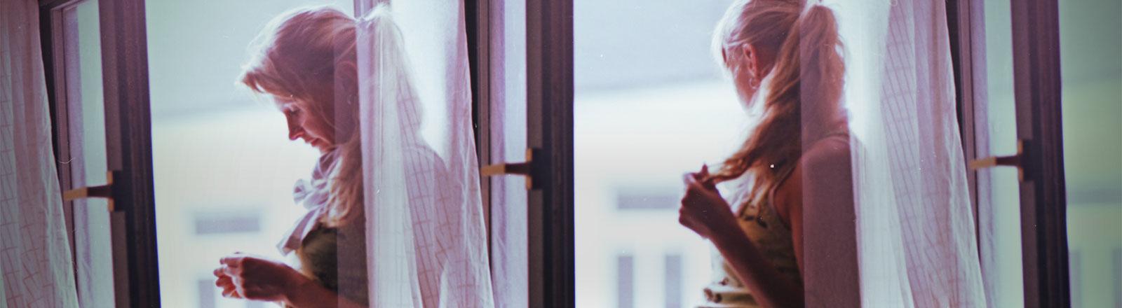 Ein Frau steht am Fenster und wartet.