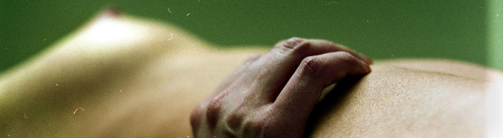 Eine Hand liegt auf einem Körper.