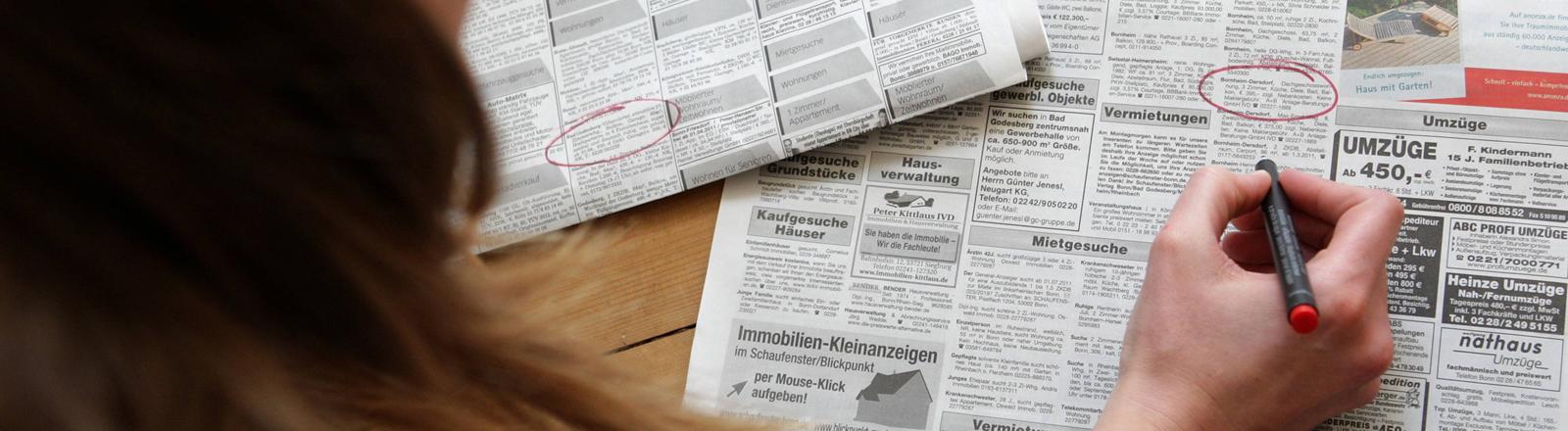 Frau liest Wohnungsangebote in der Zeitungen