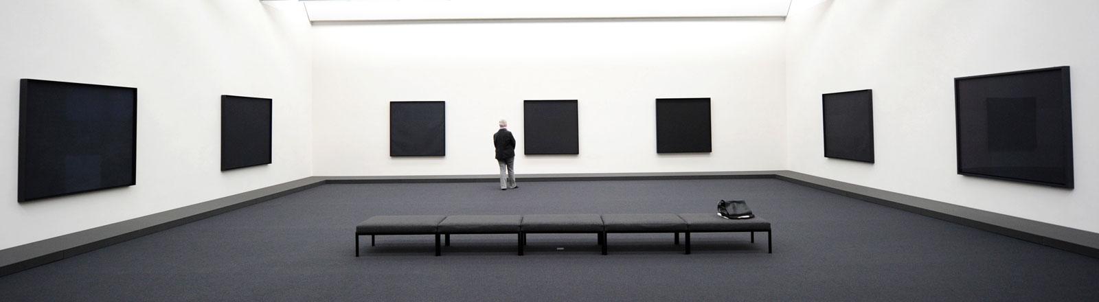 Eine Frau steht am Freitag (24.09.2010) vor Bildern des US-Konstruktivisten Ad Reinhardt im Josef Albers Museum Quadrat in Bottrop.
