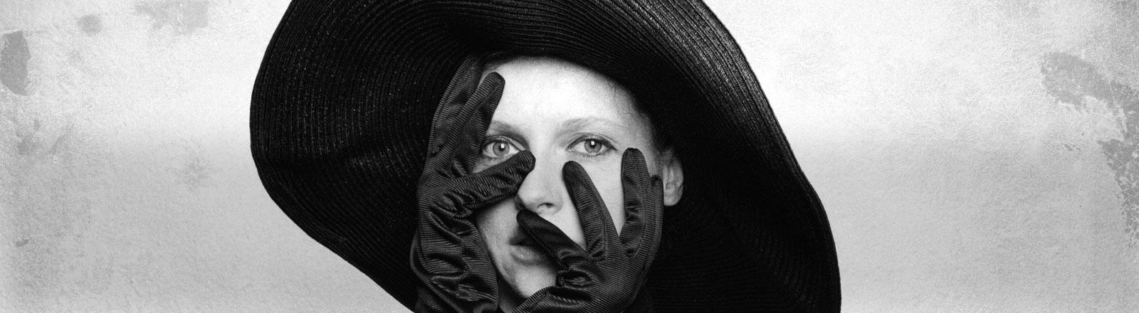 Eine Frau mit einem schwarzen Handschuhen und einem schwarzen Hut.