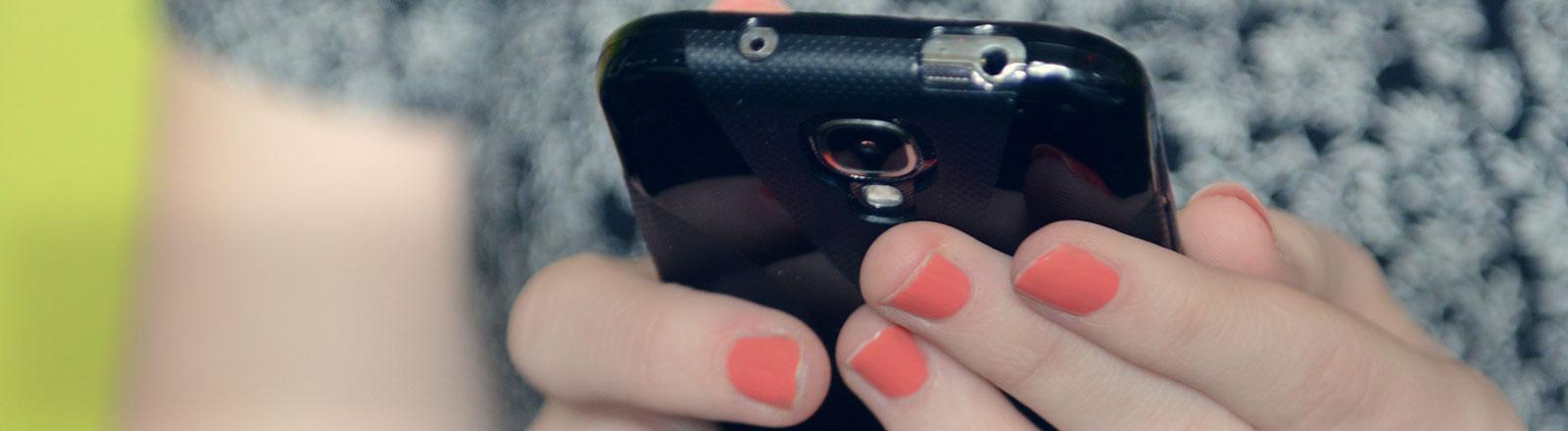 Eine Frau hält ein Smartphone in ihren Händen.