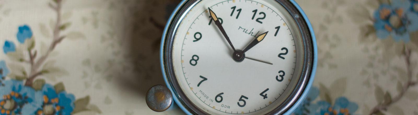 Eine Uhr, auf der die Zeiger auf kurz vor eins stehen.