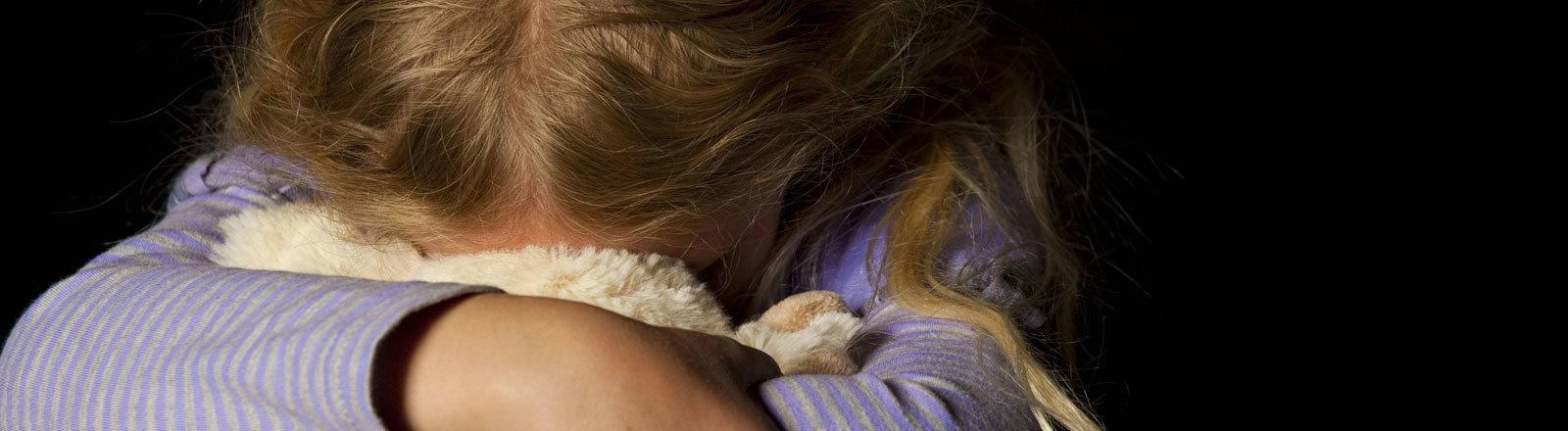 Mädchen vergäbt sein Gesicht in einem Kuscheltier