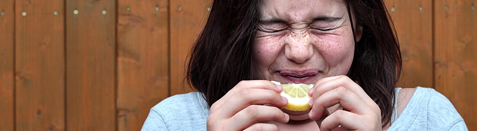 Ein Mädchen kneift die Augen zusammen und hält sich eine saure Zitrone vor das Gesicht.