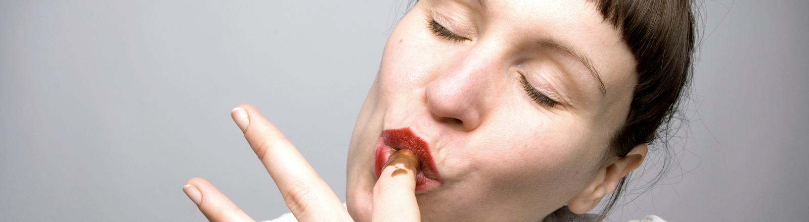 Eine Frau leckt sich genüsslich den Finger ab, an dem Schokolade klebt.