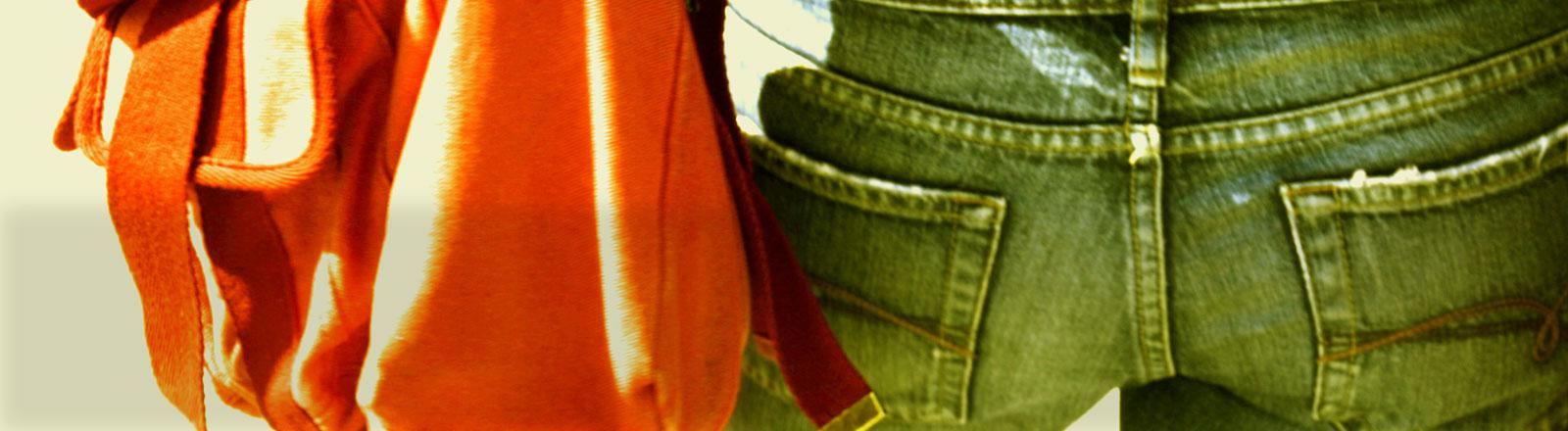Man sieht den Hintern einer Frau und ihre Handtasche, die auf Hüfthöhe hängt.