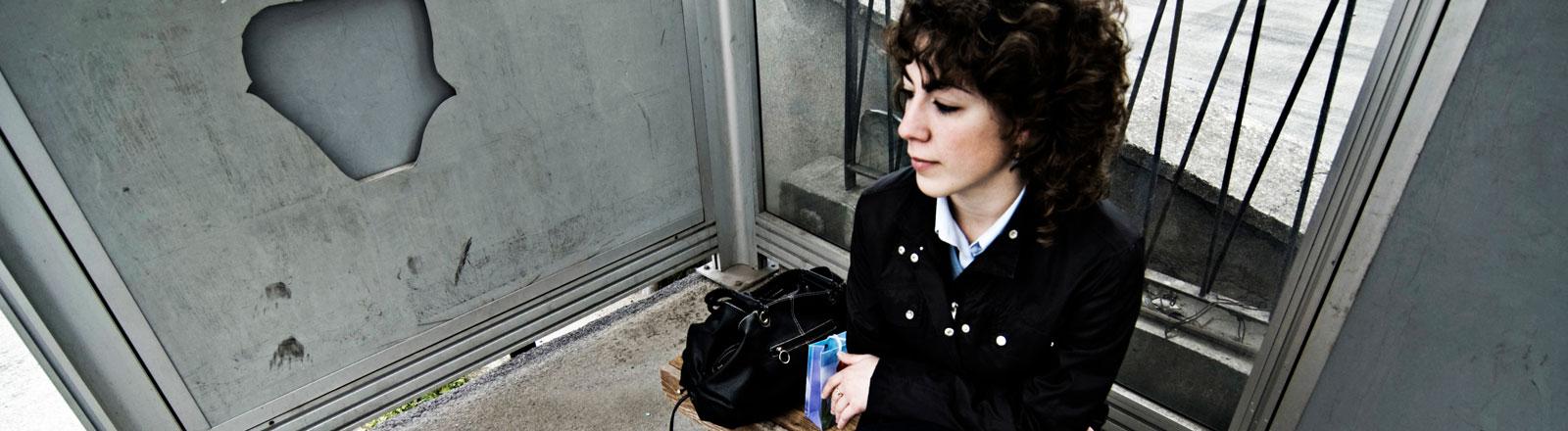 Eine Frau sitzt an einer Bushaltestelle