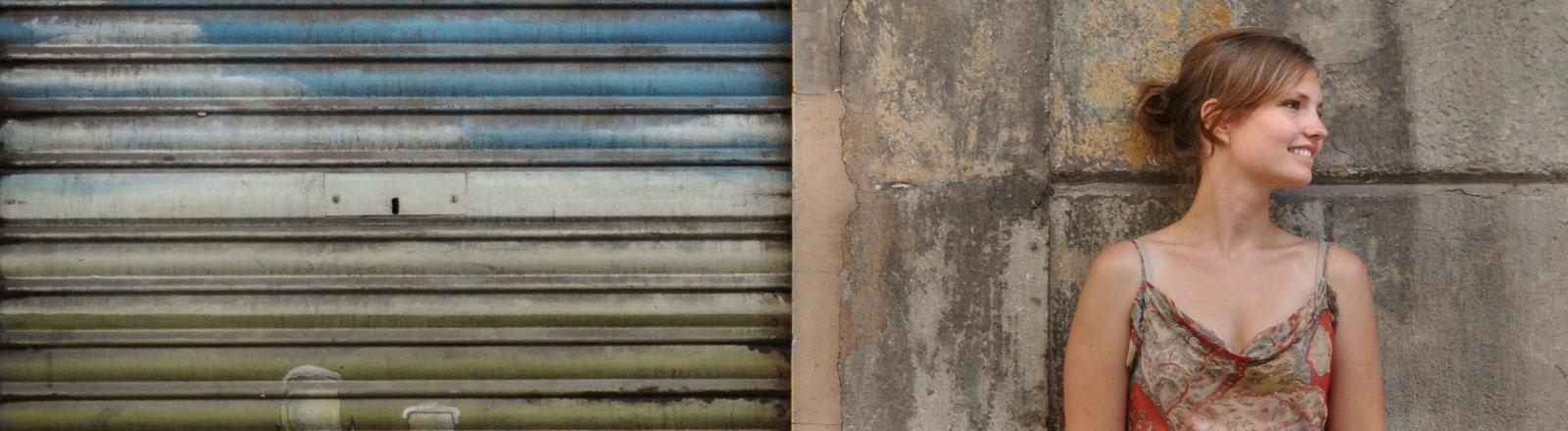 Eine Frau steht alleine vor einer Mauer.