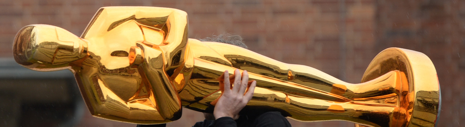 Ein Mann trägt eine großformatige Oscarstatue auf der Schulter.