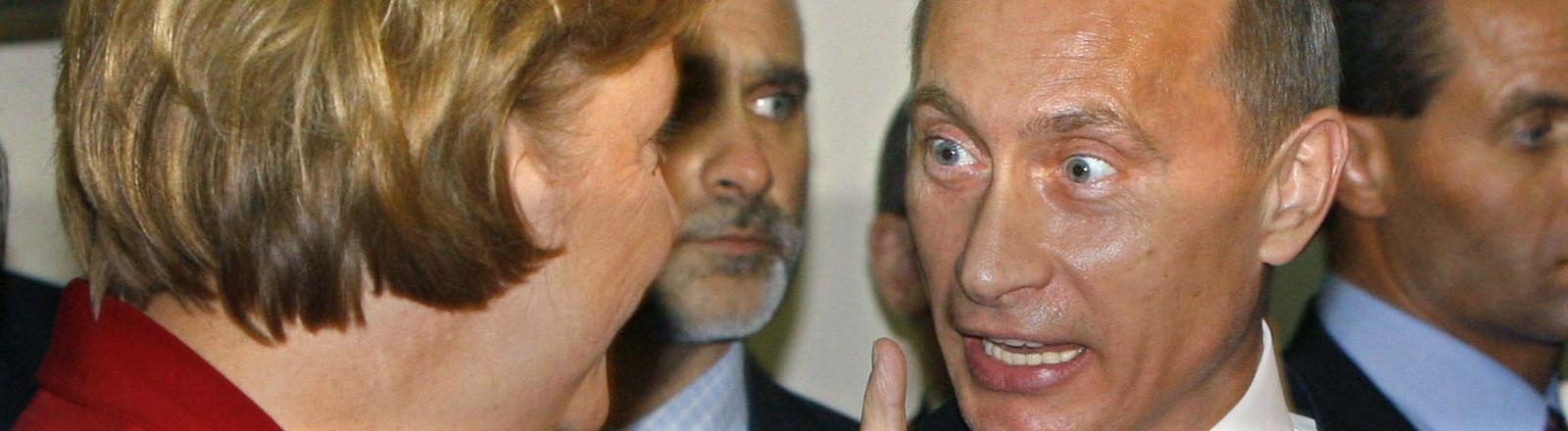Wladimir Putin guckt Angela Merkel mit wahnsinnigem Blick und erhobenem Zeigefinger an.