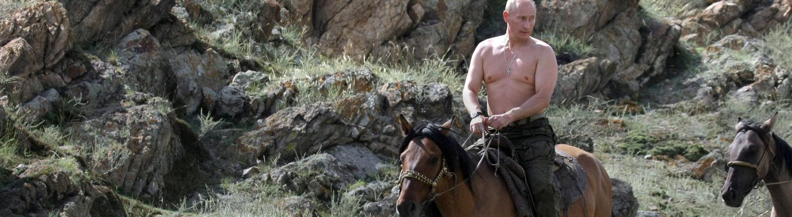 Wladimir Putin reitet mit nacktem Oberkörper auf einem braunen Pferd.
