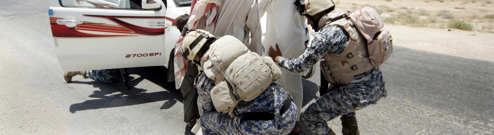 Irakische Soldaten tasten Passanten an einem Checkpoint zwischen Karbala und Ramadi ab.