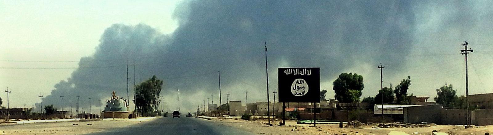 Die brennende Raffinerie in Baidschi im Irak wurde von Isis eingenommen. Im Vordergrund die Isis-Fahne.