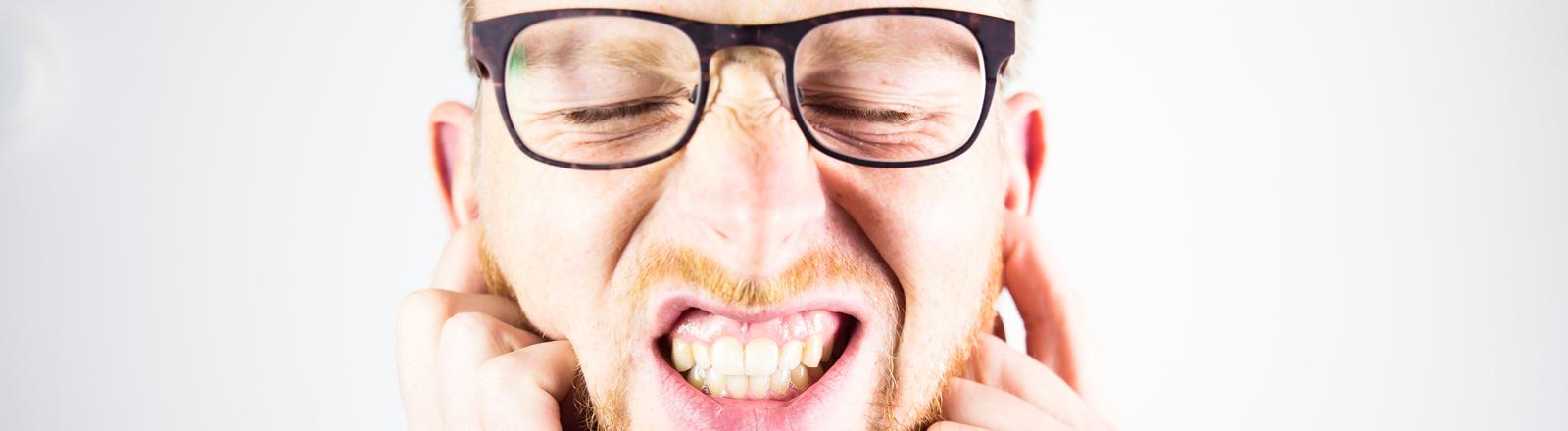 Ein Mann hält sich die Ohren zu und die Augen fest verschlossen