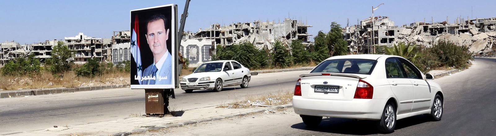 DPA: Assad Poster auf einer Straße im zerbombten Homs.