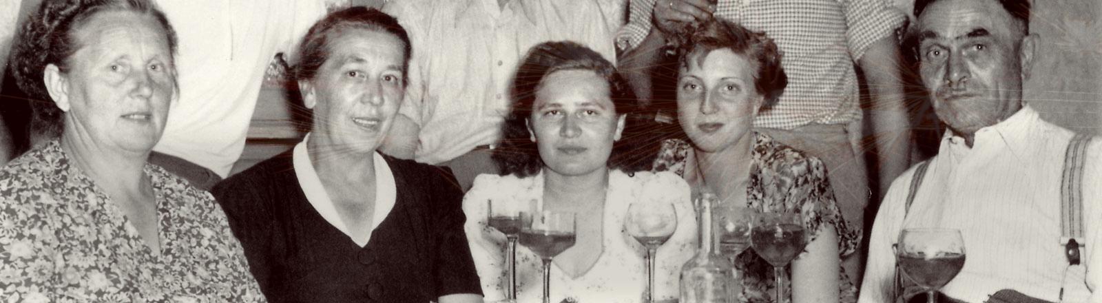 Ein altes Schwarz-Weiß-Bild einer Familie, die an einem Tisch sitzt.